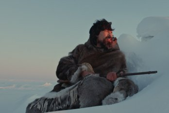 Inuit man sitting on snow while hunting