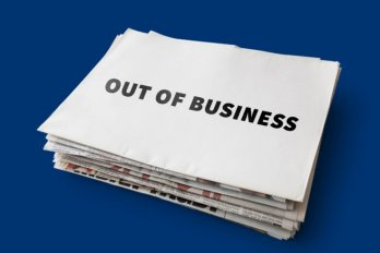 "Stack of newspapers that say ""Out of Business."""