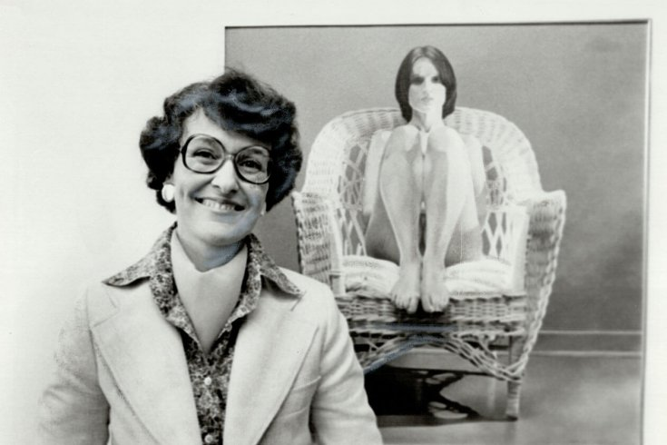 Woman posing in front of painting of woman in a chair