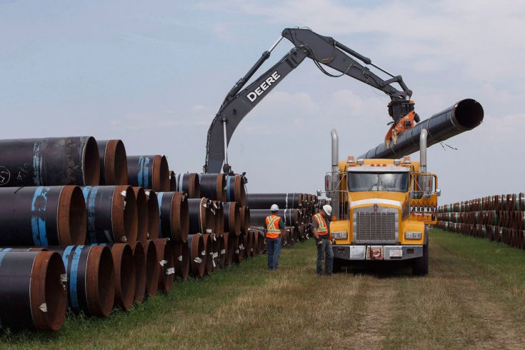 Crane loading up giant pipe onto a yellow tractor trailer