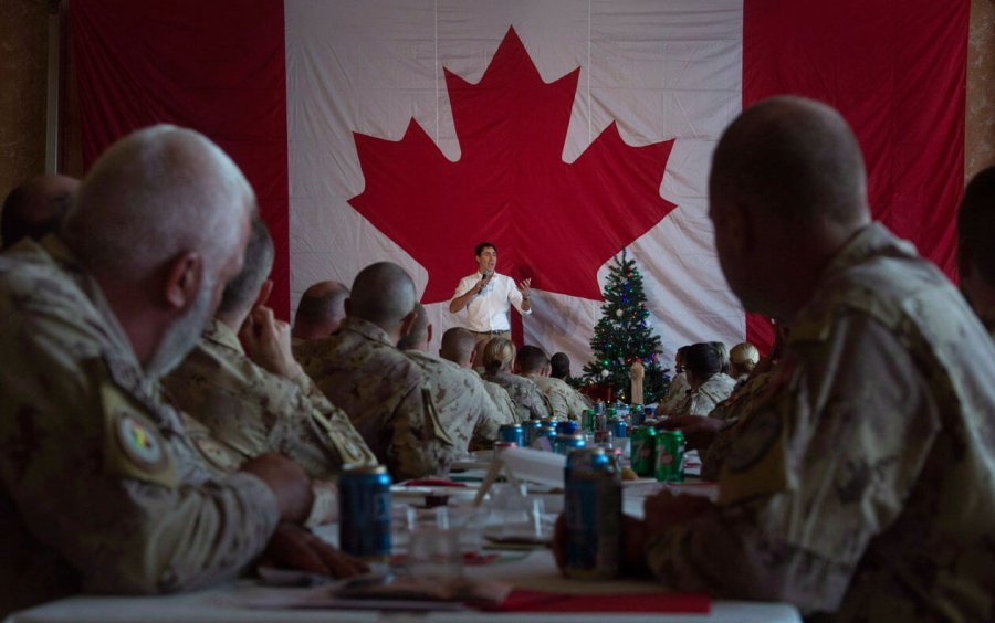 Justin Trudea stands in front of a Canadian flag and beside a Christmas tress while soldiers watch, seated.
