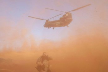 A helicopter lands while a soldier in the foreground covers his head.