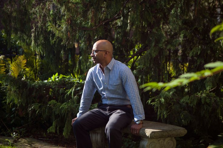 Man sitting down on stone bench near trees
