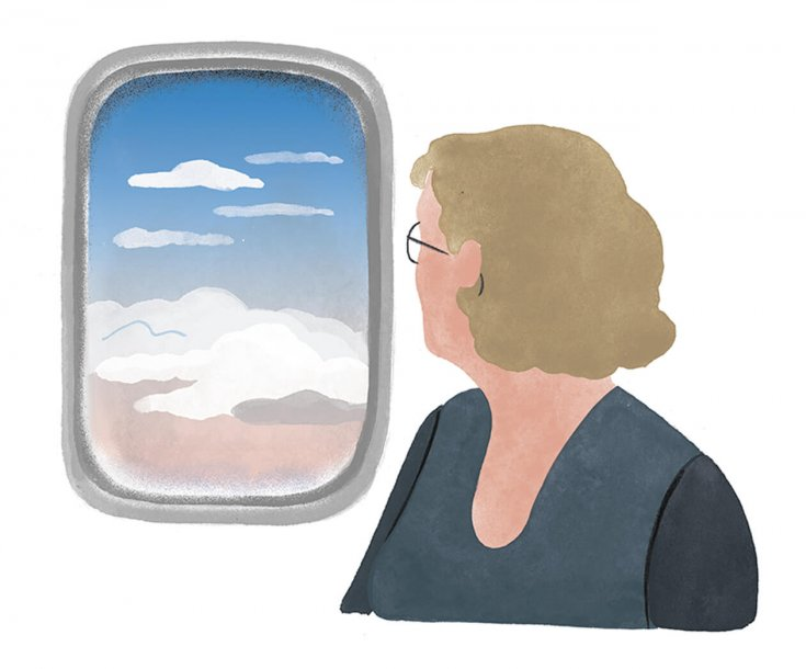 Woman looks out airplane window.