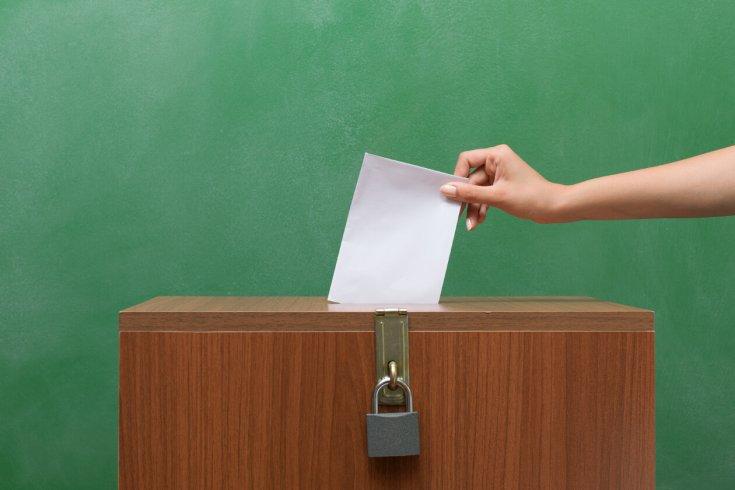 someone puts a ballot into a ballot box