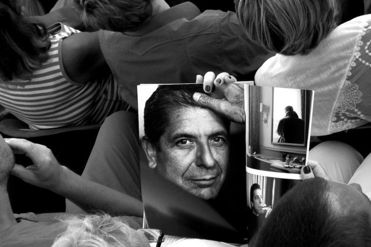 Photograph of a Woman Looking at a Leonard Cohen Themed Magazine Spread