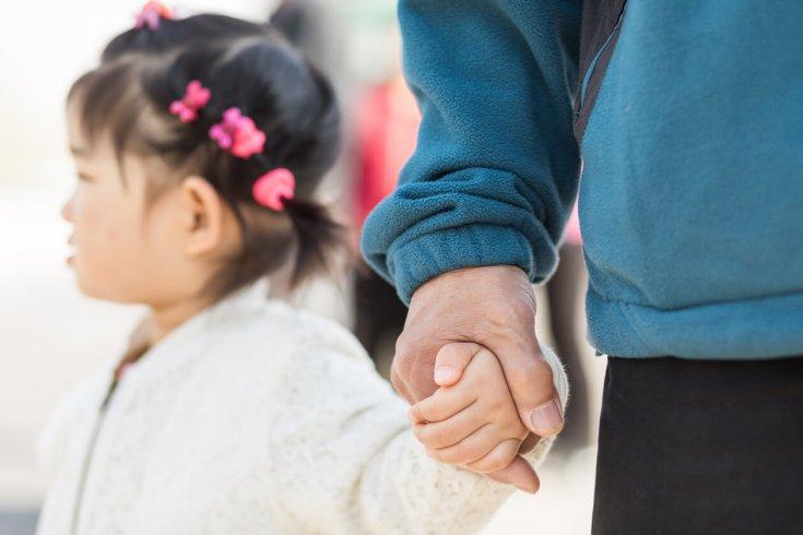 Grandparent holding hand of child