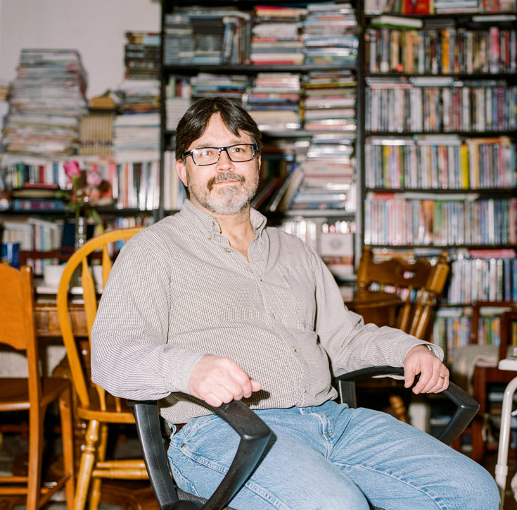 A middle-aged man in jeans and a button-up sits in a desk chair. In the background are several full bookshelves and a wooden dining table set.