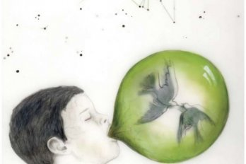 boy blowing bubbles with birds inside of it.