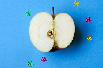 halved apple sits on a blue backdrop