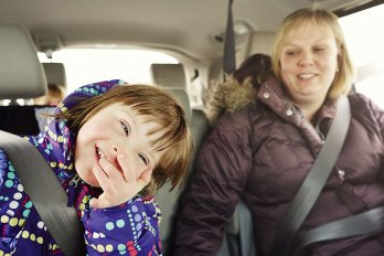 Kid smiling laughing with an adult in a car