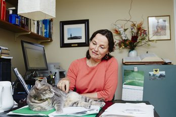 A woman sitting at a desk, petting her cat