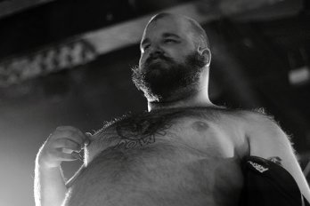 Shirtless, bearded man in front of stage lights