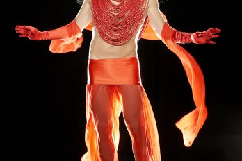 A body in a costume in front of a black background