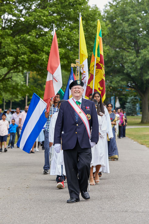 The procession carries flags and follows a smiling older man in a Knights of Columbus uniform.