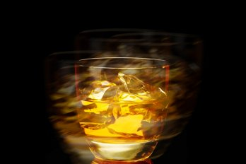 A blurred photo of an old-fashioned glass containing several cubes of ice and an amber liquid, against a black background.