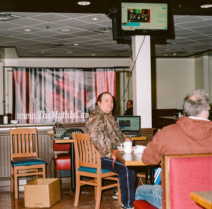An older man sits at a table in a restaurant, beneath a television.