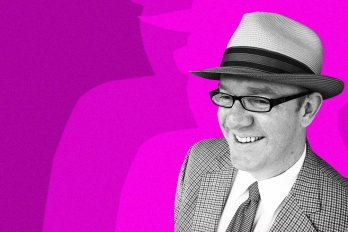 A man wearing a checkered blazer, glasses, and a fedora smiles and stares downward, against a bright pink background.