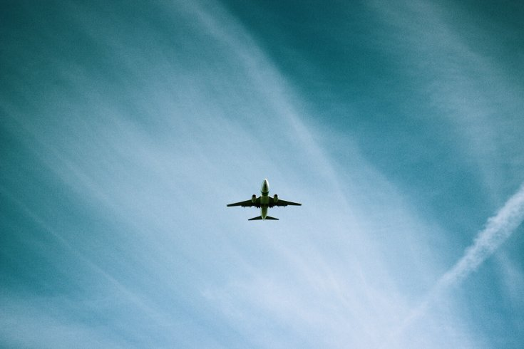 Photo of a plane in the air against a cloudy blue sky.