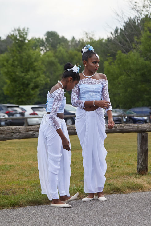 Two young dancers in long white dresses, with lace sleeves, stand waiting before the procession.