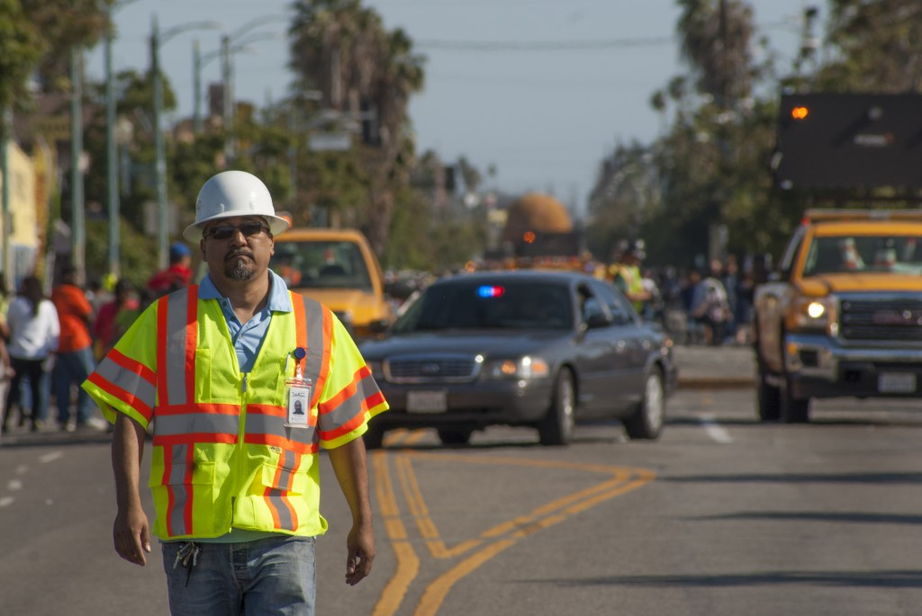 A Wiring Connection worker walks down the middle of the street as security vehicles and law enforcement begin to prepare the crowds at Vermont Avenue and 43rd Street for ET-94's arrival.