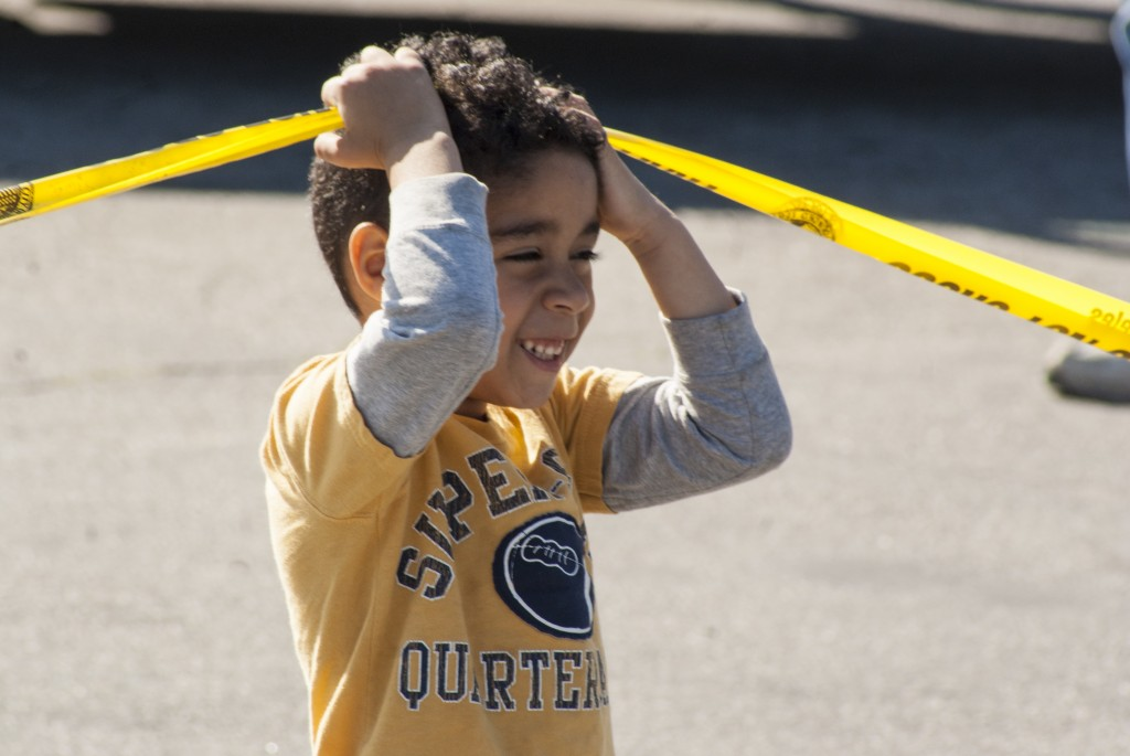 A little boy plays with caution tape while waiting for ET-94s arrival along Vermont Avenue. (Marisa Zocco / USC Annenberg Media)