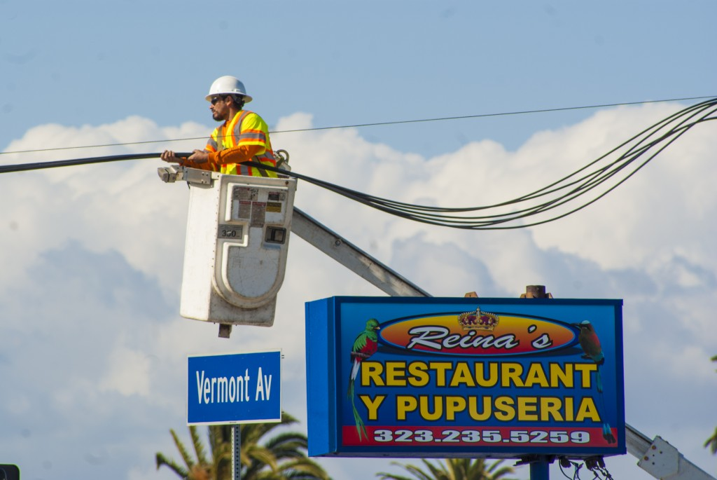 A Wiring Connection workers hovers high above the ground as the company lowers cables so that ET-94 can pass the intersection at Vermont Avenue and 43rd Street in South Los Angeles. (Marisa Zocco / USC Anenberg Media)