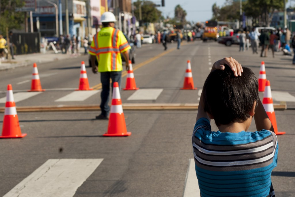 A little boy looks on and shades his scalp from the bright sun while waiting for ET-94 just visible down Vermont Avenue. (Marisa Zocco / USC Annenberg Media)