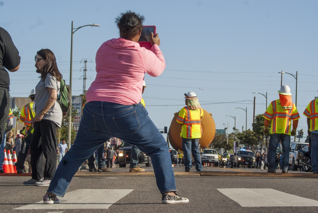 A community member quickly breaks a rule, stepping off the sidewalk to get a good shot of the approaching external tank. (Marisa Zocco / USC Annenberg Media)