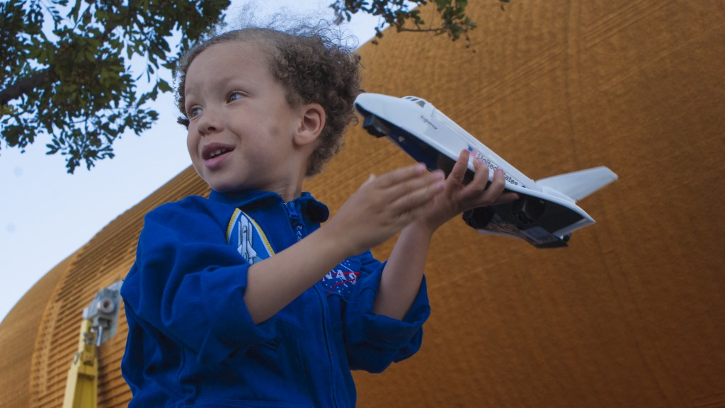 A 4-year-old boy plays with his Endeavor model shuttle as a real external tank passes in front of him. (Marisa Zocco / USC Annenberg Media)