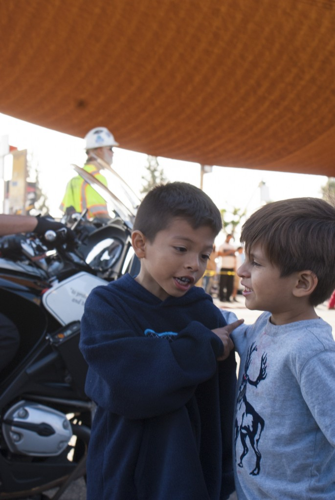 Two little boys talk about the tank while preparing to pose for their parents' camera. (Marisa Zocco / USC Annenberg Media)