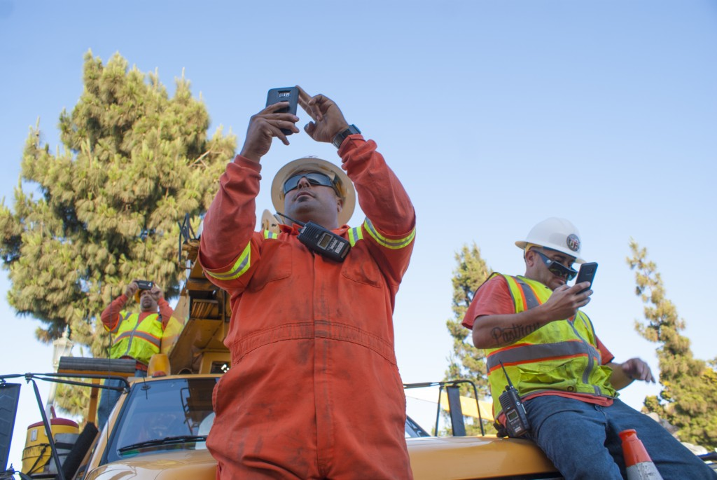 Crew members perch atop a service truck to take photos of ET-94 as it pulls into Bill Robertson Lane. (Marisa Zocco / USC Annenberg Media)