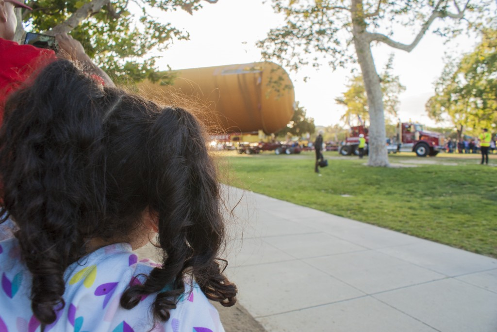 A pig-tailed little girl looks on as ET-94 pulls into the lawn behind the Los Angeles County Museum of Natural History. (Marisa Zocco / USC Annenberg Media)