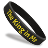 black wristband with yellow ink filled text saying The King In Me