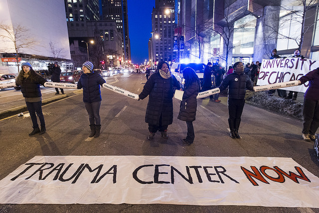 In this photo taken March 5, 2015, demonstrators link arms and block Michigan Avenue, calling for the University of Chicago to reopen a trauma center on the South Side which the University closed in 1988. (flickr/Scott L)