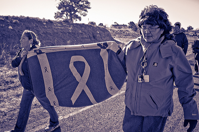 Members of the Navajo Nation Advisory Council Against Domestic Violence lead a march (flickr/Donovan Shortey)