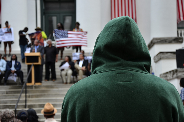 A man with hoodie watches the speakers on the steps of the Historic Capital Building in Tallahassee, Florida at a Rally March for Trayvon Martin (Flickr/Stephen Nakatani)