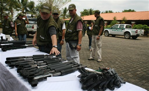 Police display seized weapons on property confiscated from former paramilitary boss and drug lord Carlos Mario Jimenez, alias 'Macaco,' in 2009. (AP/William Fernando Martinez)