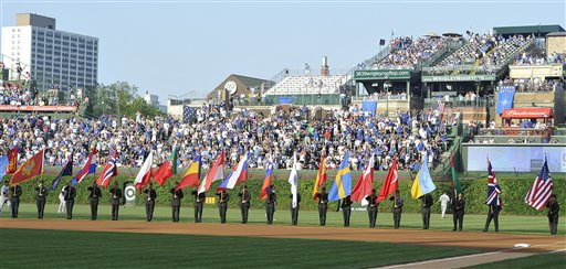 Flags representing the NATO countries are displayed at Wrigley Field in a pregame ceremony before the Cubs/Sox game Saturday. (AP/Jim Prisching)