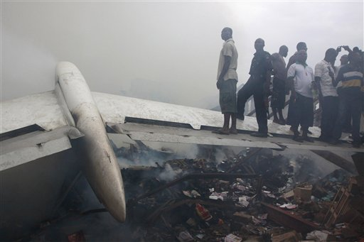 People stand on a wing of a wrecked passenger plane in Lagos, Nigeria on June 3, 2012. The plane crashed in a densely populated neighborhood near the airport. (AP/Sunday Alamba)