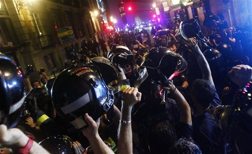 Firefighters hold up their helmets during a protest against austerity measures announced by the Spanish   government in Madrid, Spain, Thursday July 19, 2012. (AP/Andres Kudacki)
