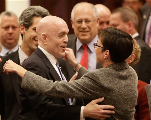 AP (Illinois Rep. Greg Harris, D-Chicago, left, is congratulated by lawmakers as gay marriage legislation passes on the House floor during veto session Tuesday, Nov. 5, 2013, in Springfield Ill. Illinois Gov. Pat Quinn, top center, looks on.)