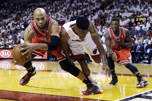 Chicago Bulls forward Taj Gibson, left, and Miami Heat guard Norris Cole battle for a loose ball as guard Nate Robinson, far right, watches during the first half of Game 2 of their NBA basketball playoff series. (AP/File)