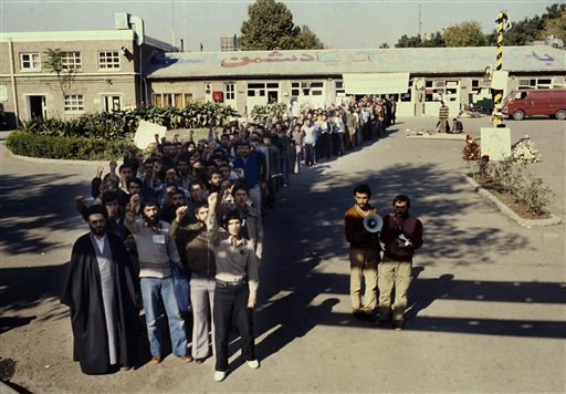 Crowd of Iranian men stand outside the U.S. Embassy compound in Tehran, Iran, where a number of U.S. citizens were taken as hostages, Nov. 1979. (AP Photo)