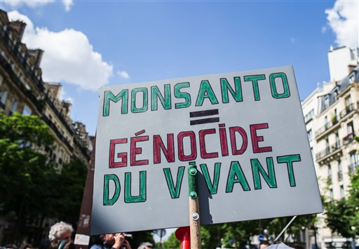A banner is photographed, during a World March Against Monsanto, in Paris, France, in Paris, Saturday, May 23 2015. Marches and rallies against Monsanto, a sustainable agriculture company and genetically modified organisms food and seeds were held in dozens of countries in a global campaign highlighting the dangers of GMO Food. Banner reads 'Monsanto genocide alive'. (AP Photo/Kamil Zihnioglu)