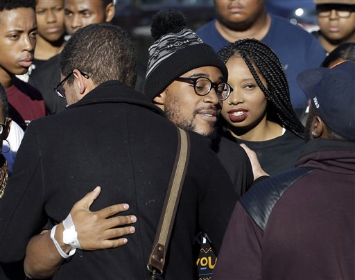 Jonathan Butler, center, hugs supporters after addressing a crowd following the announcement that University of Missouri System President Tim Wolfe would resign, Monday, Nov. 9, 2015, at the university in Columbia, Mo. Butler has ended his hunger strike as a result of the resignation. (AP Photo/Jeff Roberson)