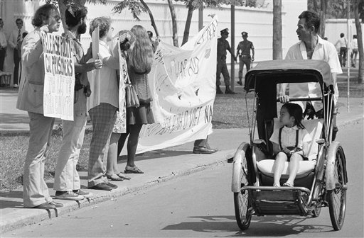 A little girl in a pedicab, and her driver stare as they pass a demonstration of nine anti-war activists before the United States embassy in Saigon, Friday, Jan. 25, 1975. The activists, led by David Harris, left, of Menlo Park, Calif. former husband of folk singer Joan Baez, passed out leaflets demanding the end of U.S. intervention in South Vietnam. (AP Photo)