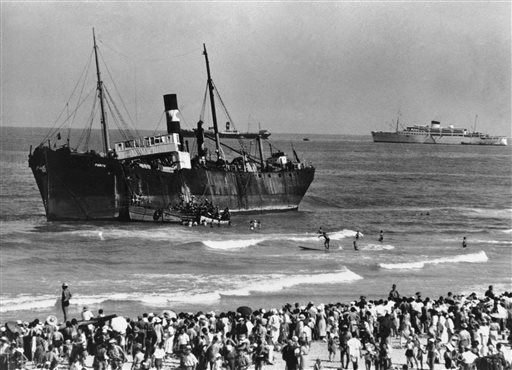 In this Aug. 22, 1939 file photo, the S.S. Parita, with 700 European Jewish refugees on board, lists after it was beached near the Ritz Hotel in Tel Aviv, an all-Jewish town in Palestine, under British mandate. The state of Israel declared independence in 1948. (AP Photo)