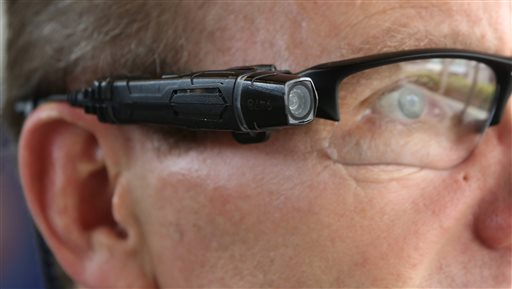 In this photo taken Thursday, Feb. 19, 2015, Steve Tuttle, vice president of communications for Taser International, demonstrates one of the company's body cameras that can be attached to glasses , for the Associated Press during a company-sponsored conference hosted by Taser at the California Highway Patrol Headquarters in Sacramento, Calif. (AP Photo/Rich Pedroncelli)