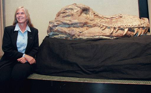 """Marine archaeologist and paleontologist Susan Hendrickson poses with her discovery of the largest Tyrannosaurus rex fossil before it sold at Sotheby's in New York, Saturday Oct. 3, 1997. Hendrickson made found """"Sue"""" while a summer intern with the Black Hills Institute of Geological Research in South Dakota in 1990. """"Sue"""" was sold to the Field Museum in Chicago. (AP Photo/Emile Wamsteker)"""